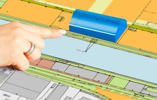 Hand zeigt auf Bauplan mit Halle