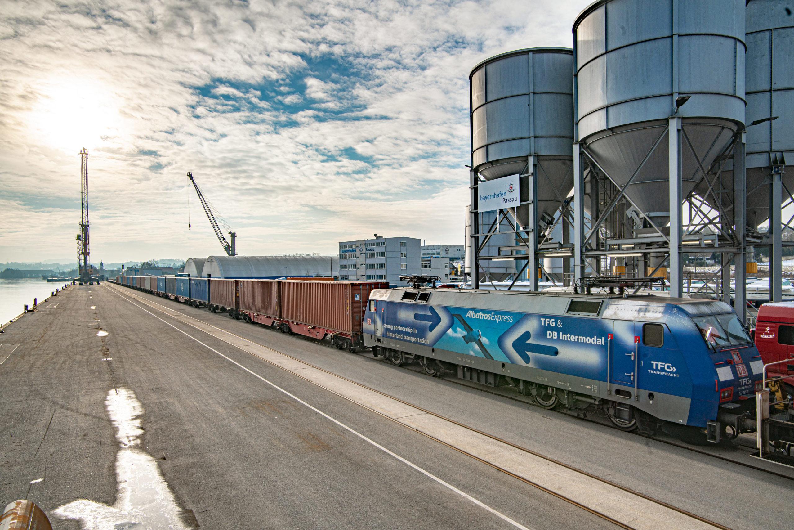 Intermodal-Containerzug am Kai des bayernhafen Passau, im Hintergrund Silos und Hafenkran