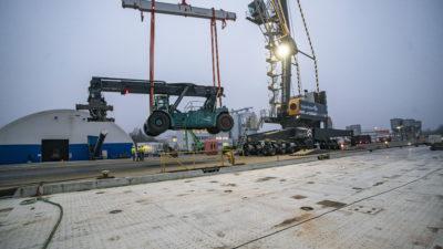 Reachstacker hängt am Haken des Hafenmobilkrans mit Schwerlast-Traverse. Im Hintergrund Lagerhallen