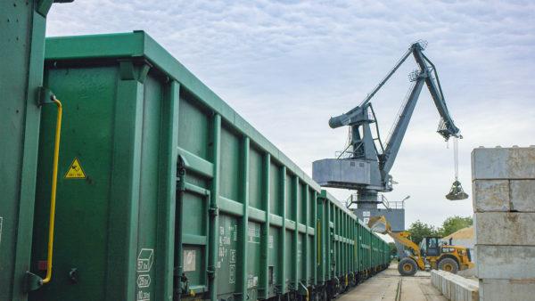 Umschlag von Erden mittels Radlader und Hafenkran in grüne Eisenbahnwaggons im bayernhafen Aschaffenburg