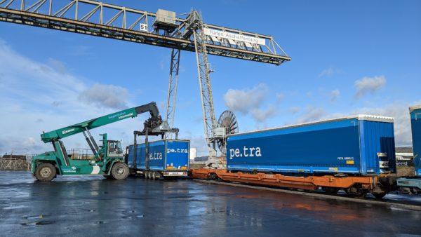 Umschlag von blauen Sattelaufliegern mittels Reachstacker auf Zug im bayernhafen Aschaffenburg