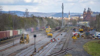 Hafenbahnhof Aschaffenburg rechts Bauarbeiten mit Gleisstopfzug, links durchfahrender Containerzug